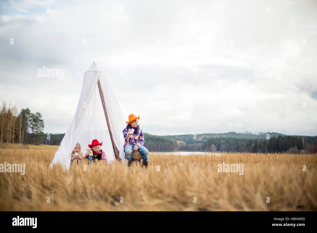 Enfants (8-9) portant des chapeaux de cow-boy sitting in tent Photo Stock