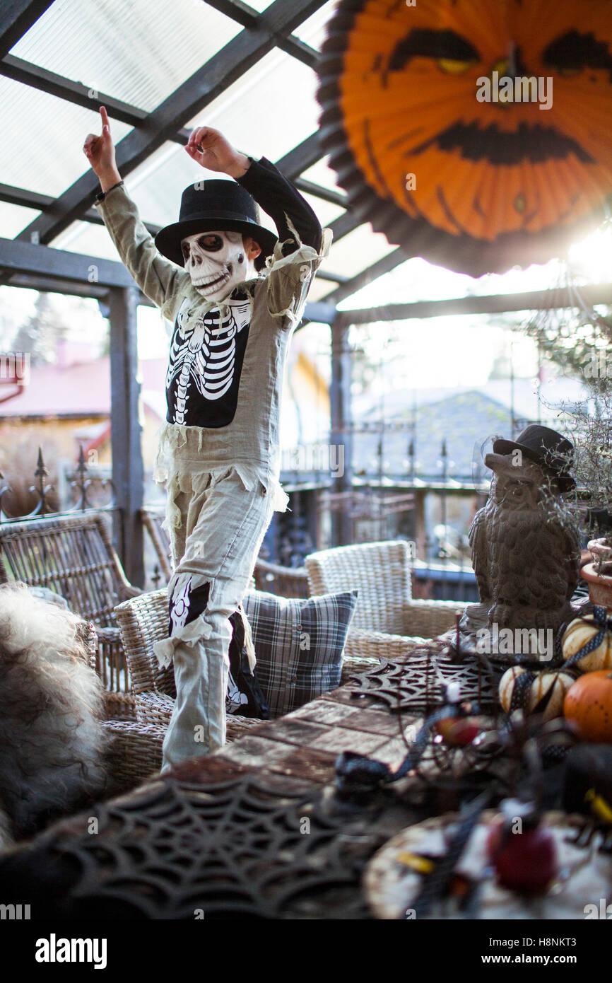 Boy (8-9) wearing costume squelette raising arms dans chambre Banque D'Images