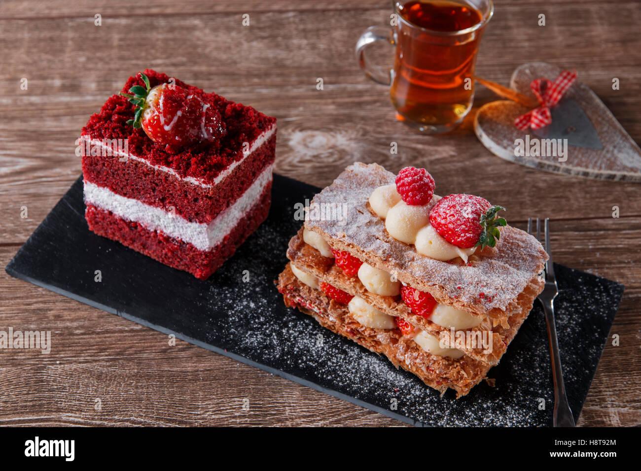 Mille feuille sweet dessert gâteau de velours rouge tranche avec le glaçage blanc est garnie de fraises Photo Stock
