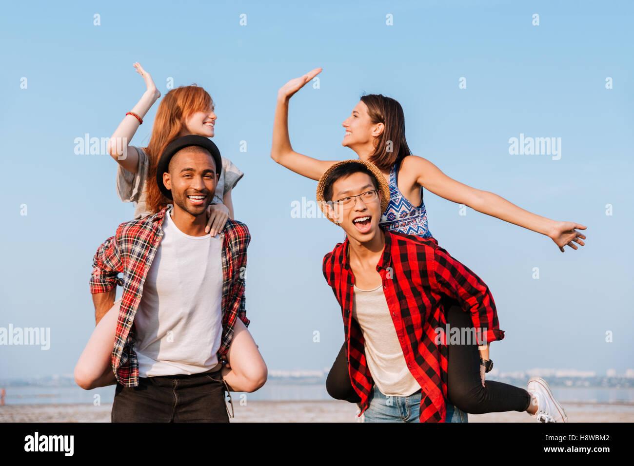 Deux jeunes couples heureux en donnant cinq élevé et s'amuser en plein air Photo Stock
