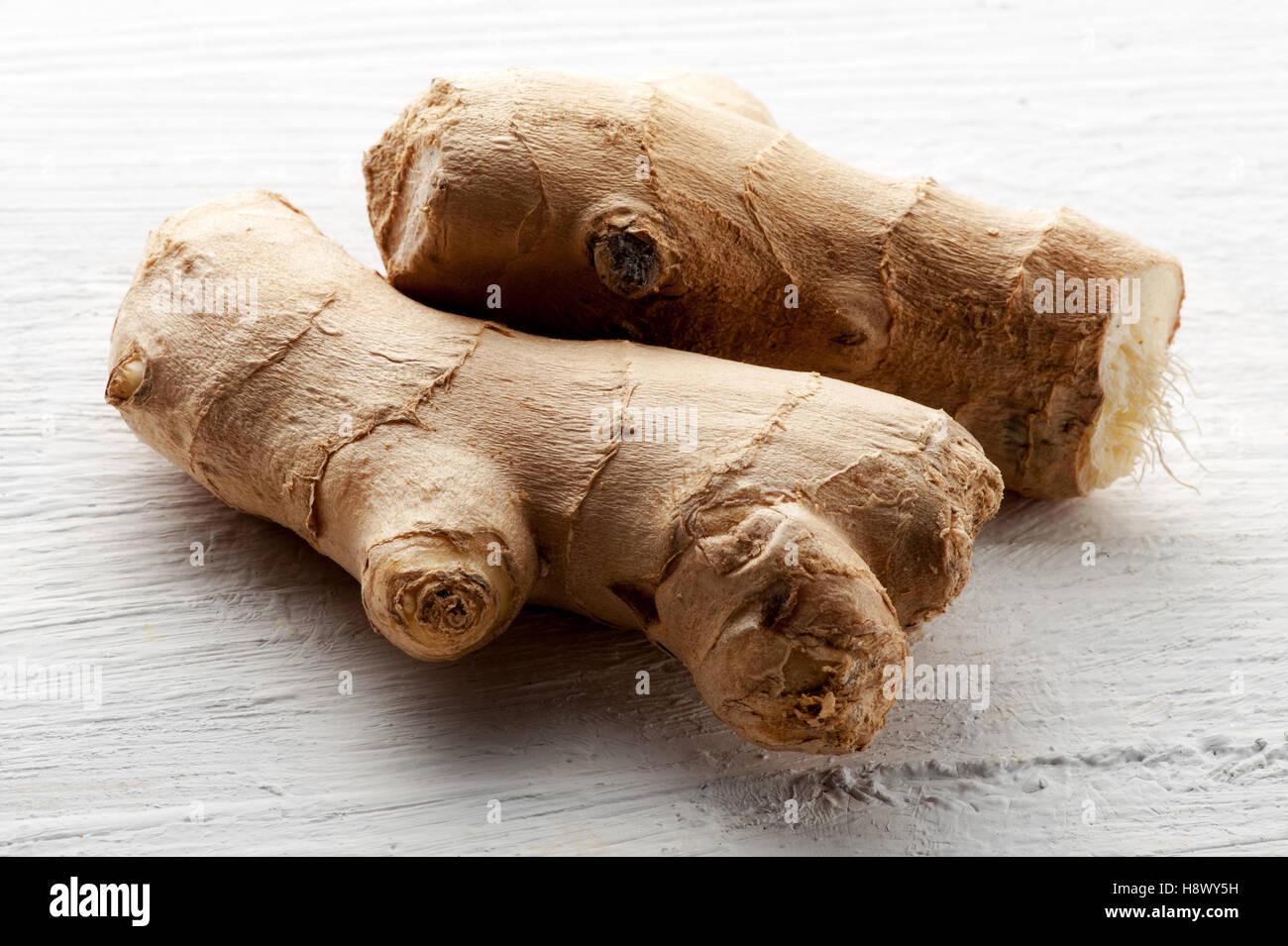 La racine de gingembre cru frais sur un tableau blanc texturé pour une utilisation en cuisine comme assaisonnement Photo Stock