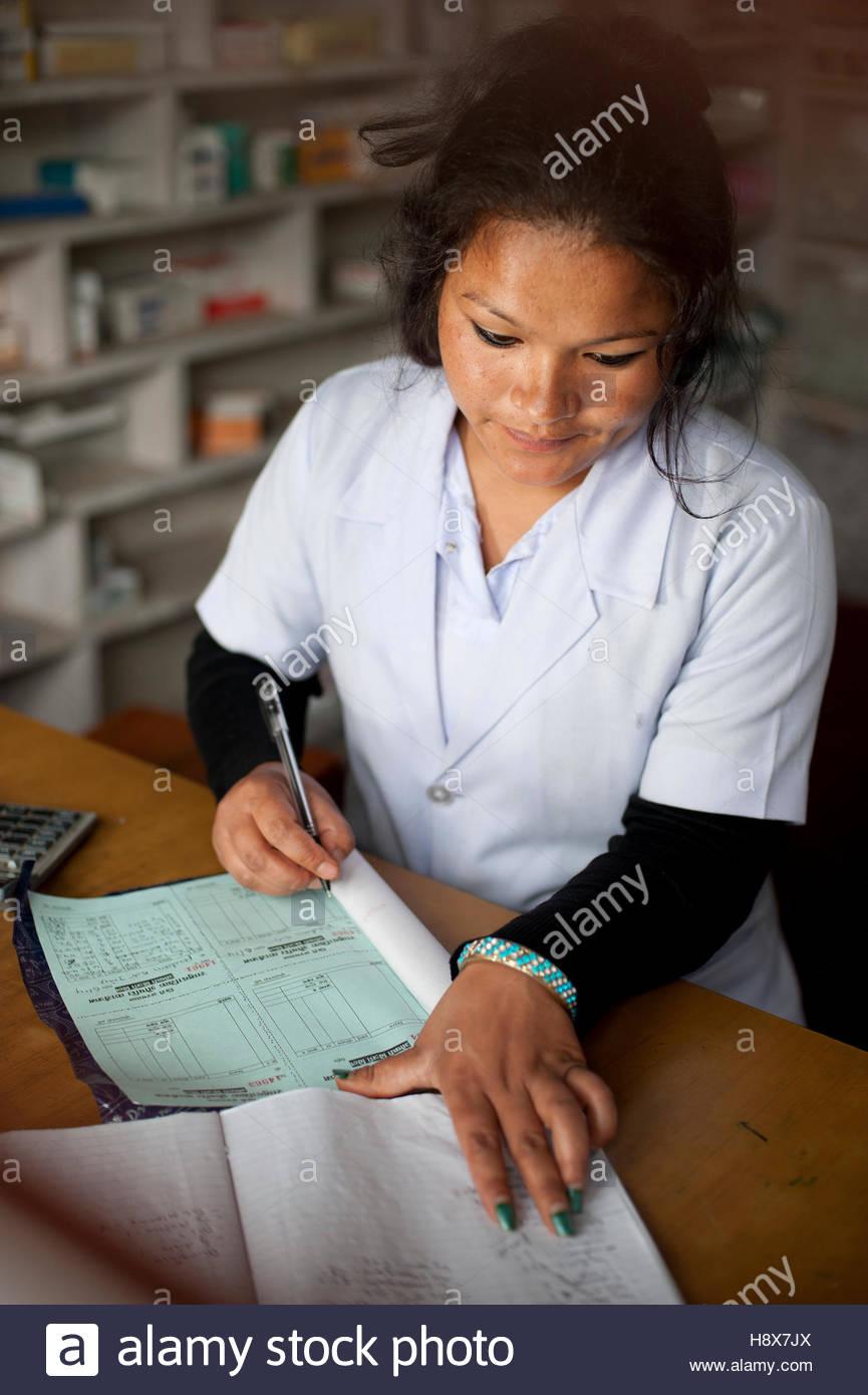Un médecin rédige une prescription de médicaments dans un hôpital au Népal. Photo Stock