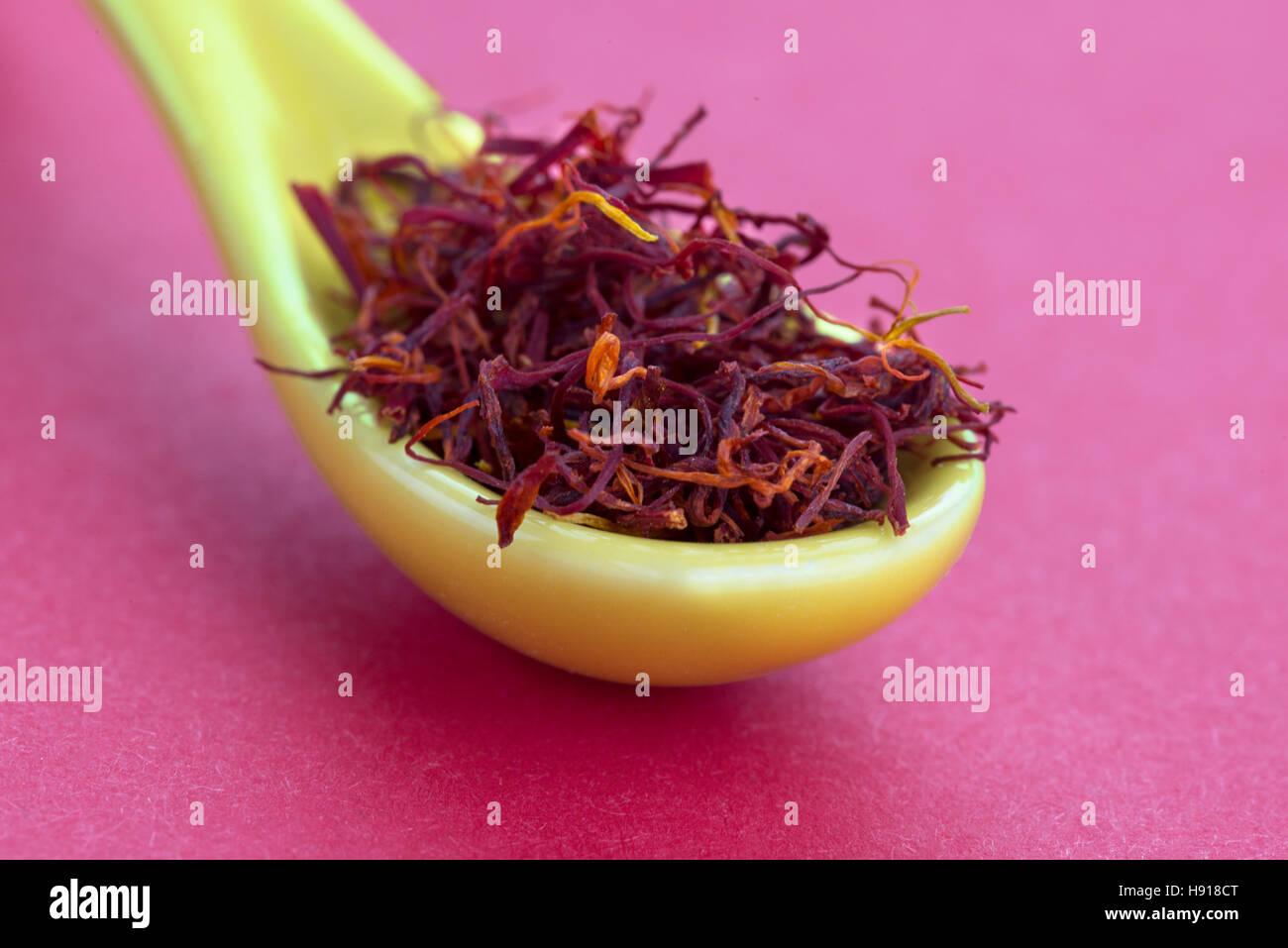 Macro shot coloré de safran dans une cuillère jaune sur un fond rouge, copie espace dessus et base Photo Stock
