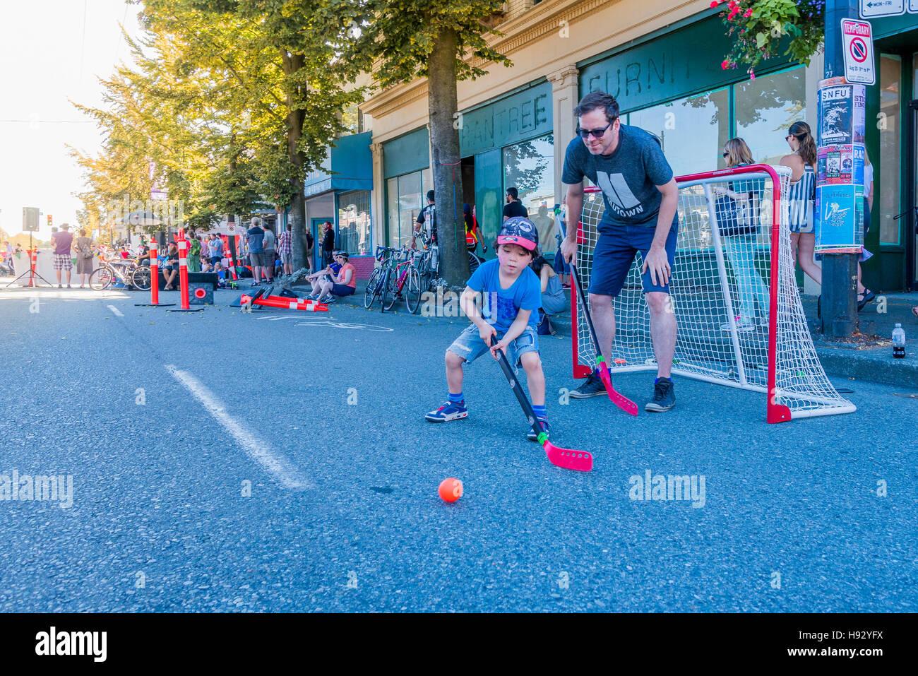 Père et fils jouant le hockey de rue, Vancouver, Colombie-Britannique, Canada, Photo Stock