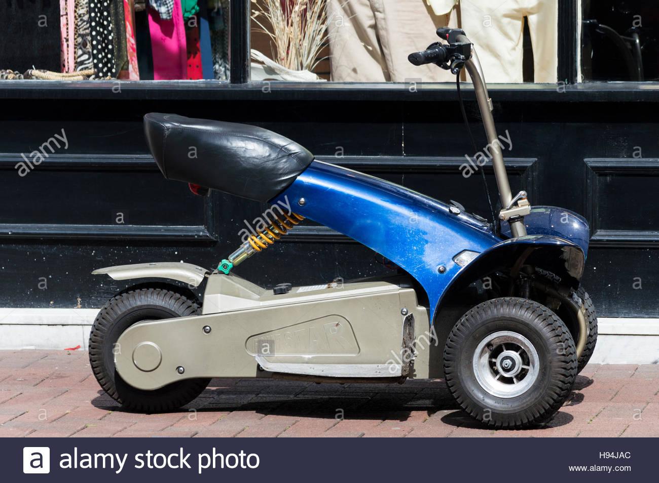 Quatre étoiles scooter de mobilité à l'extérieur d'un magasin de charité, Poole, Photo Stock