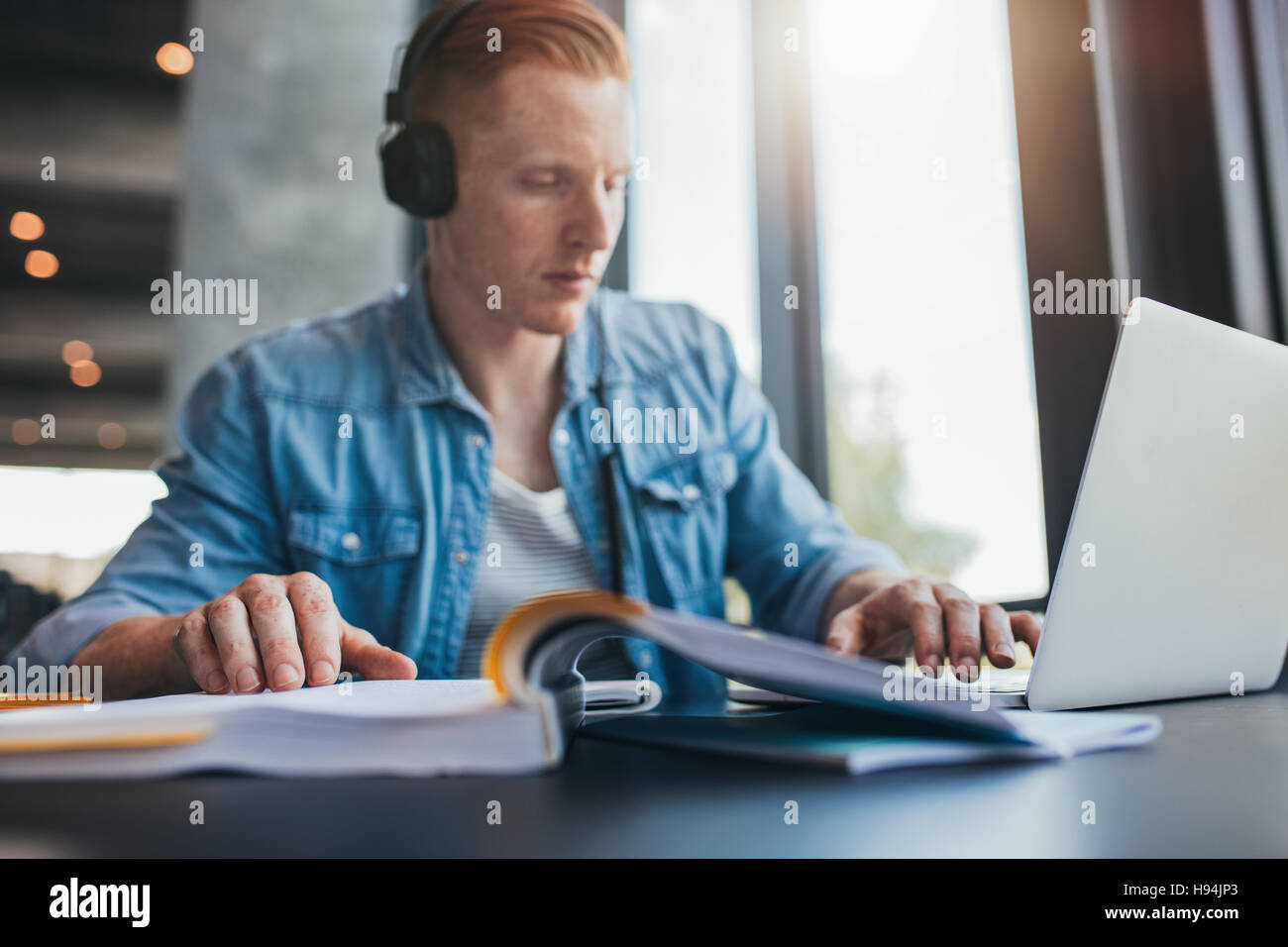 Piscine shot of male student studying in library à l'université. Jeune homme à l'aide d'ordinateur Photo Stock