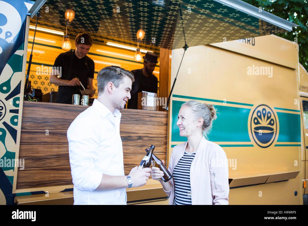 Les clients de boire une bière en face de camion alimentaire Banque D'Images