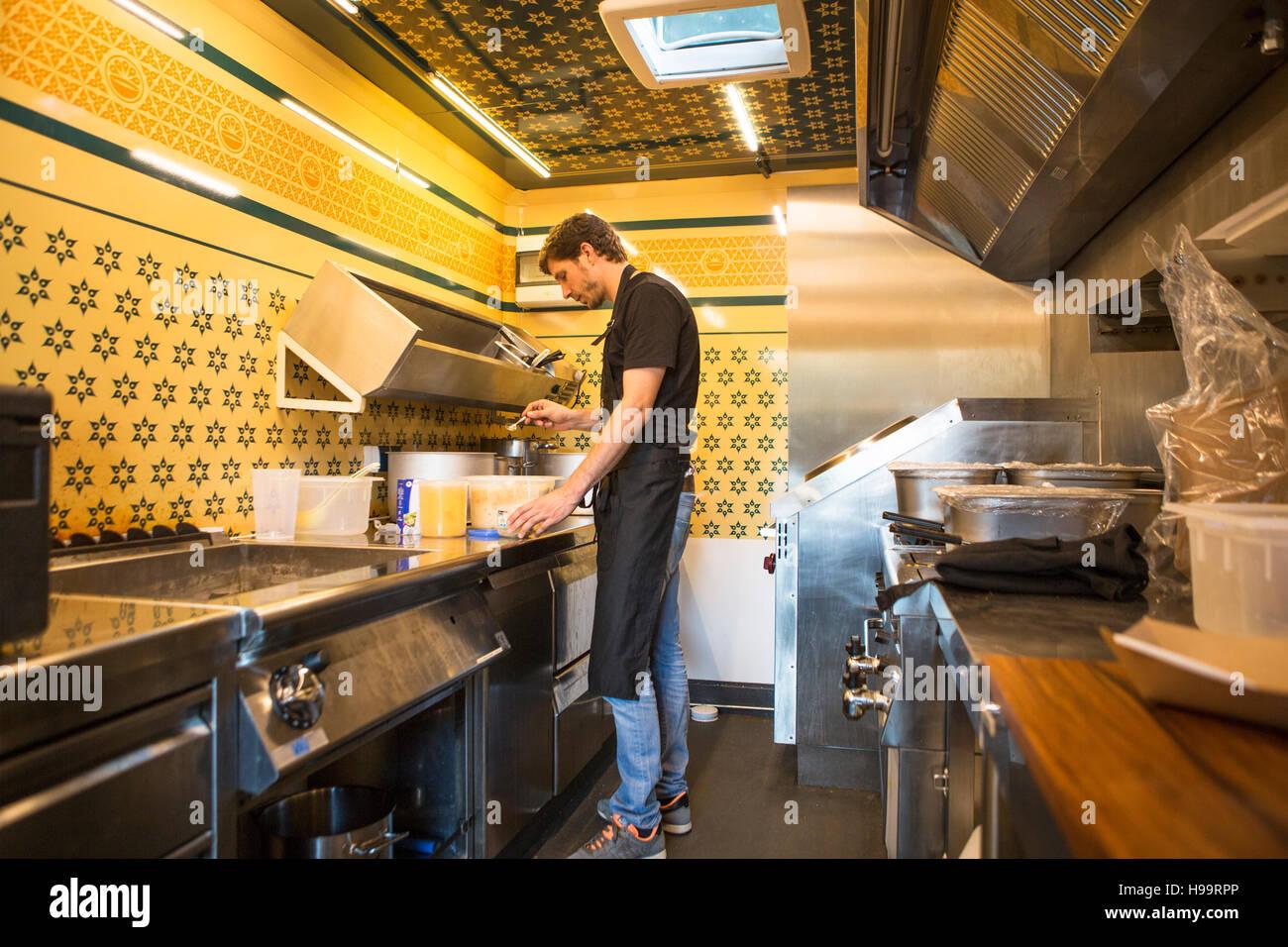 Tablier avec entrepreneur travaillant en cuisine commerciale au camion alimentaire Banque D'Images