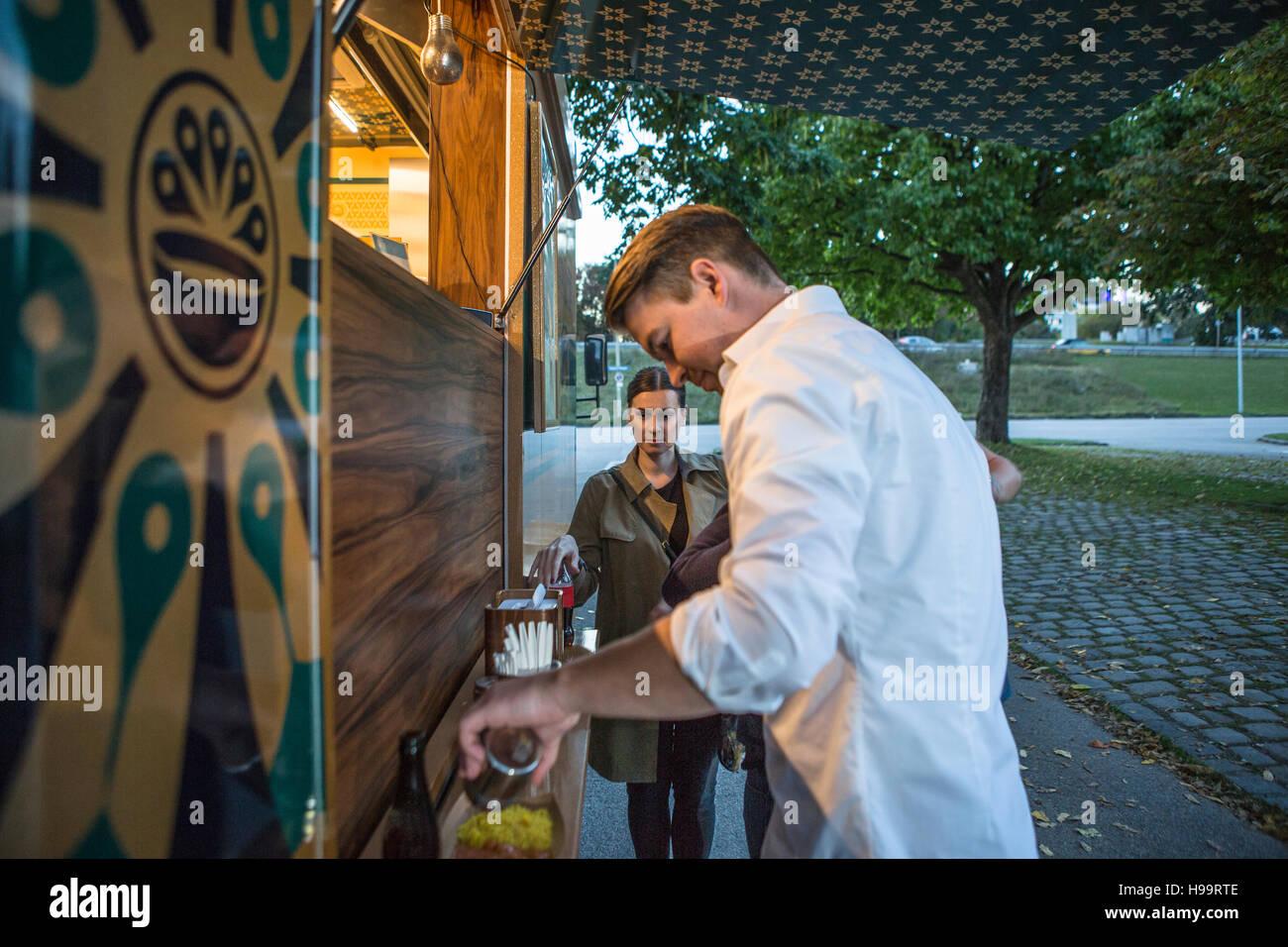 La clientèle masculine manger plat à camion alimentaire Banque D'Images