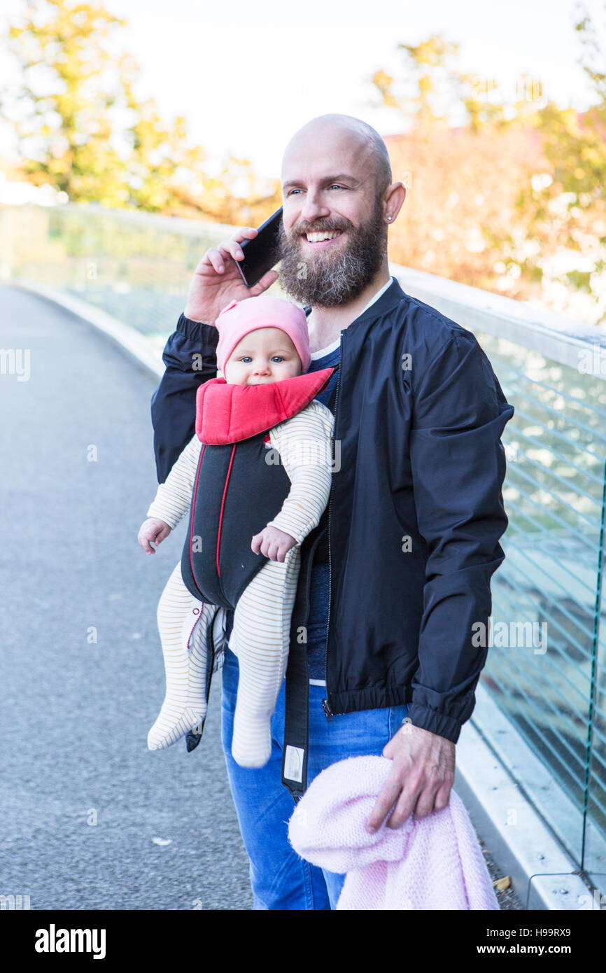 Père avec bébé en porte-bébé fille Banque D'Images