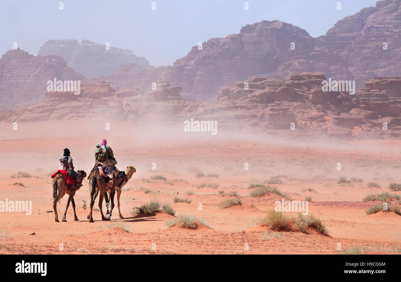 Les gens sur des chameaux en passant par la tempête du désert Photo Stock