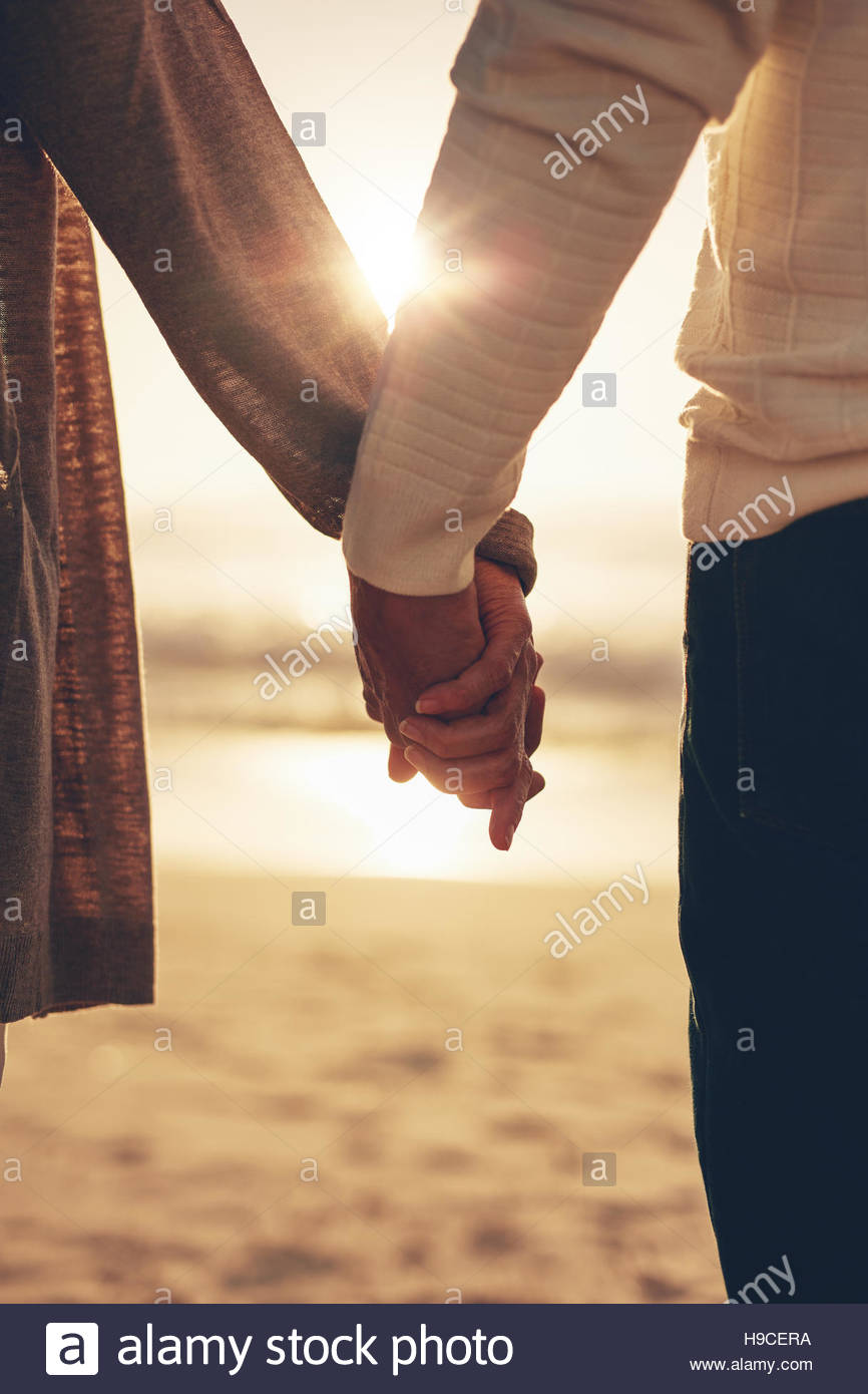 Close up portrait of a romantic senior couple holding hands contre la mer au coucher du soleil. Photo Stock