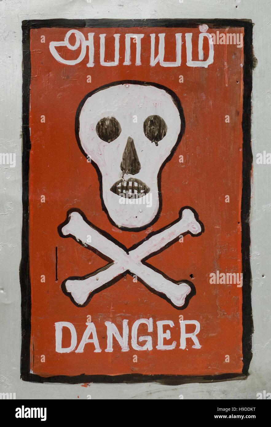 Les os du crâne et le signe de danger en tamoul et en anglais. Photo Stock