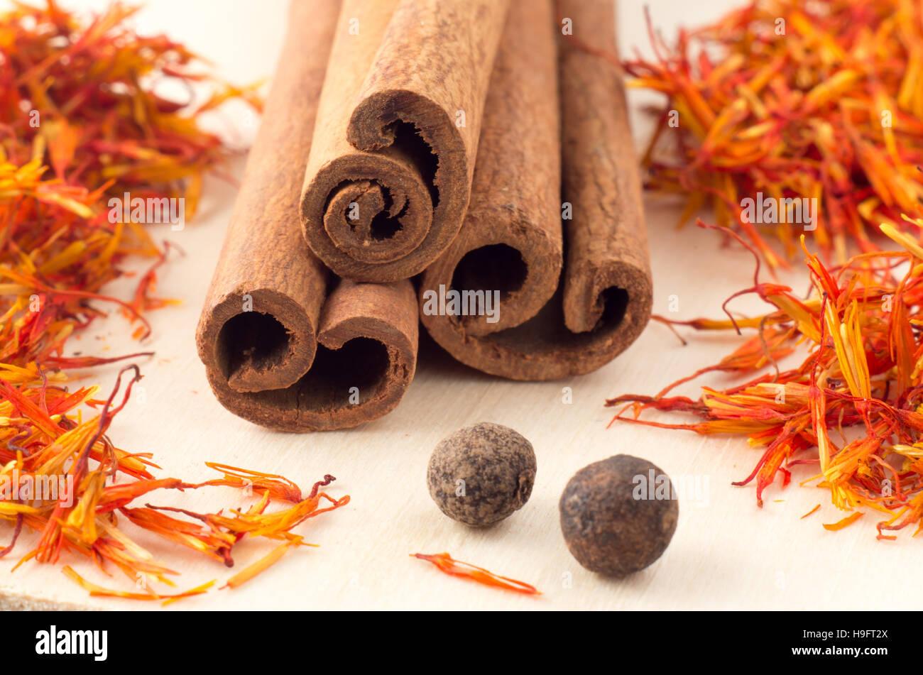 Les bâtons de cannelle, de safran et de piment aromatiques sur plateau en bois jaune close-up avec une faible Photo Stock