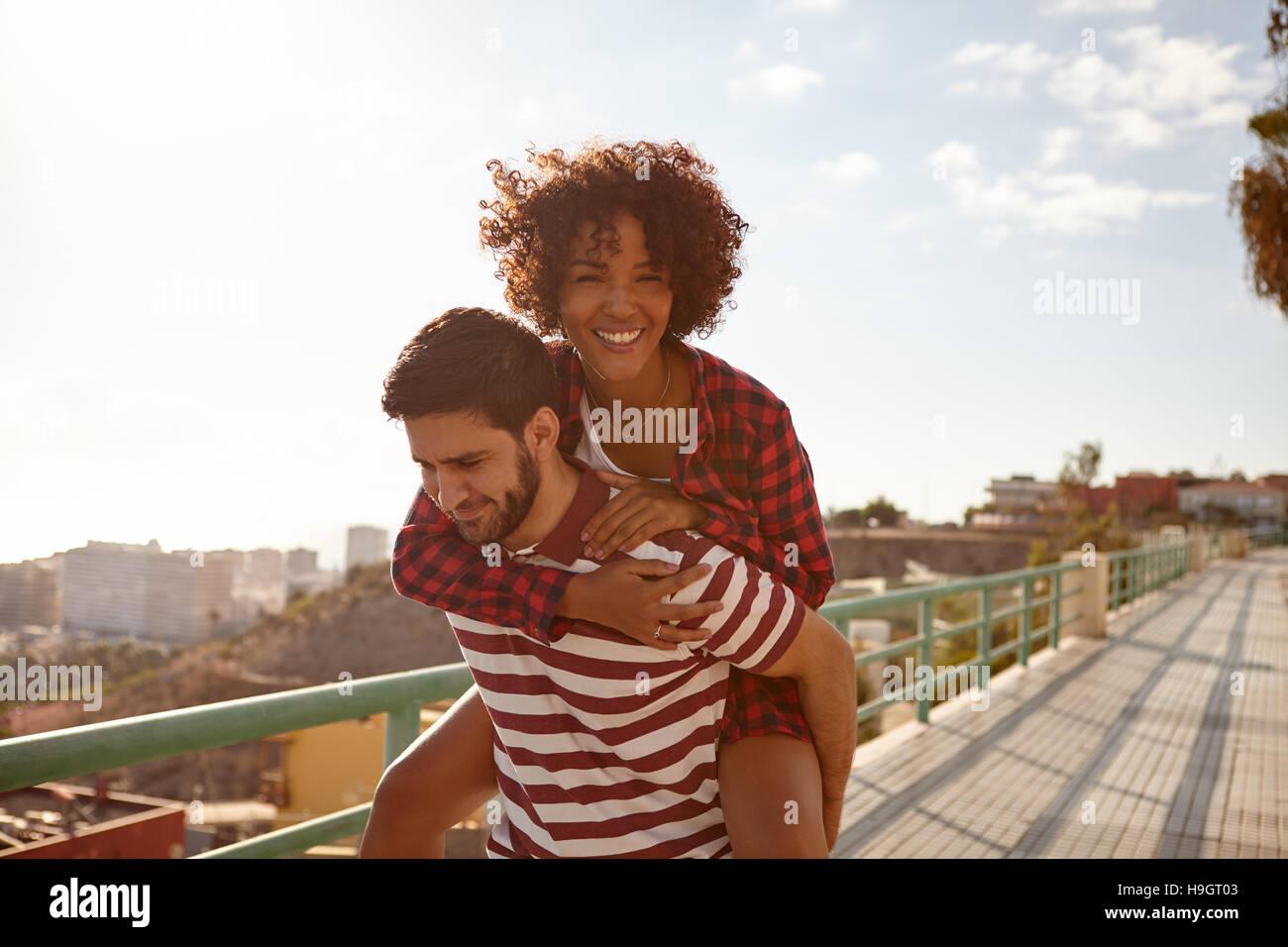 Le couple piggy back ride avec elle sur le dos, le bras droit autour de son cou, la main gauche sur son épaule Photo Stock