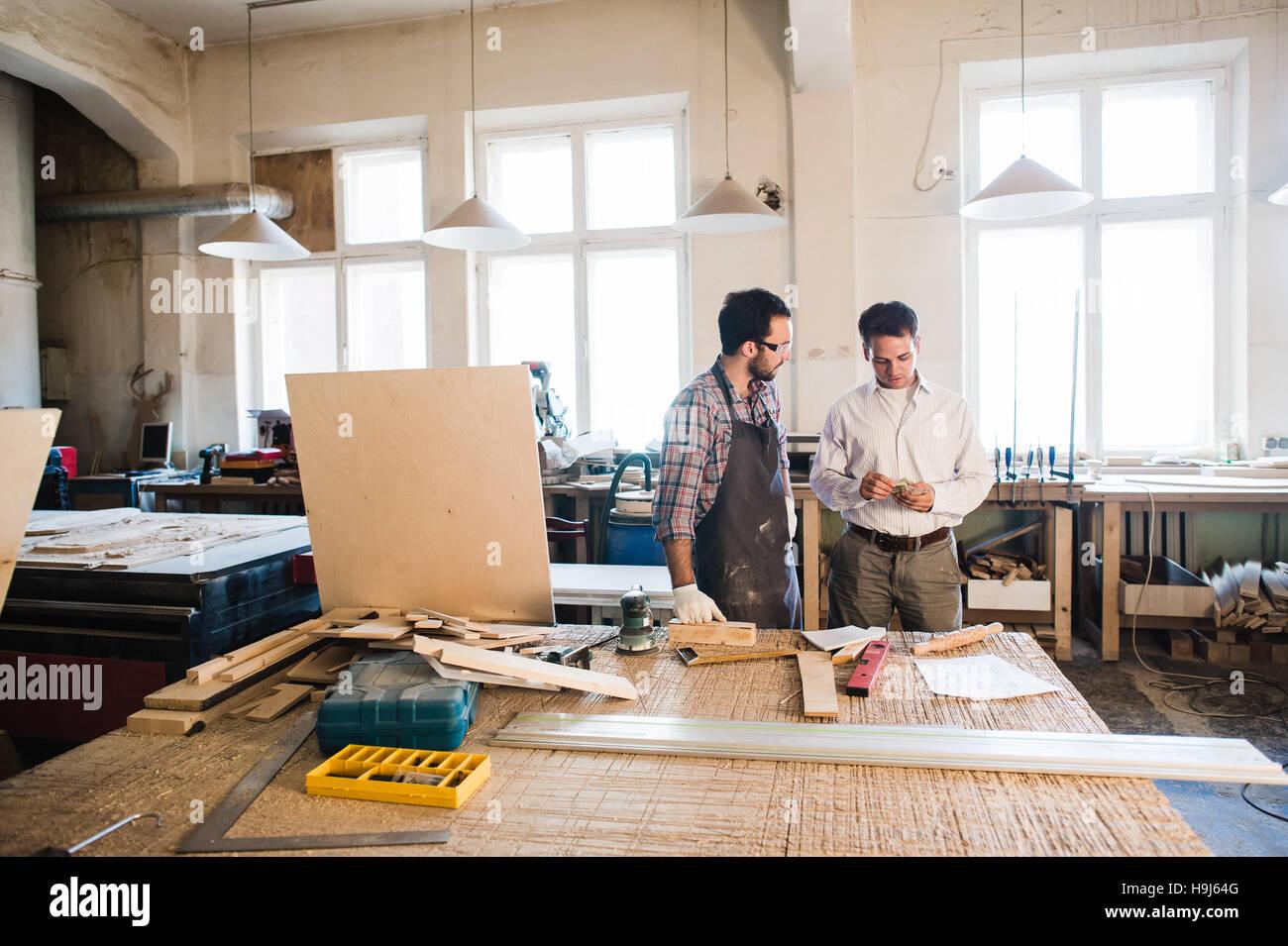 Happy male carpenter montrant quelque chose à un collègue à son carnet de papiers en atelier Photo Stock