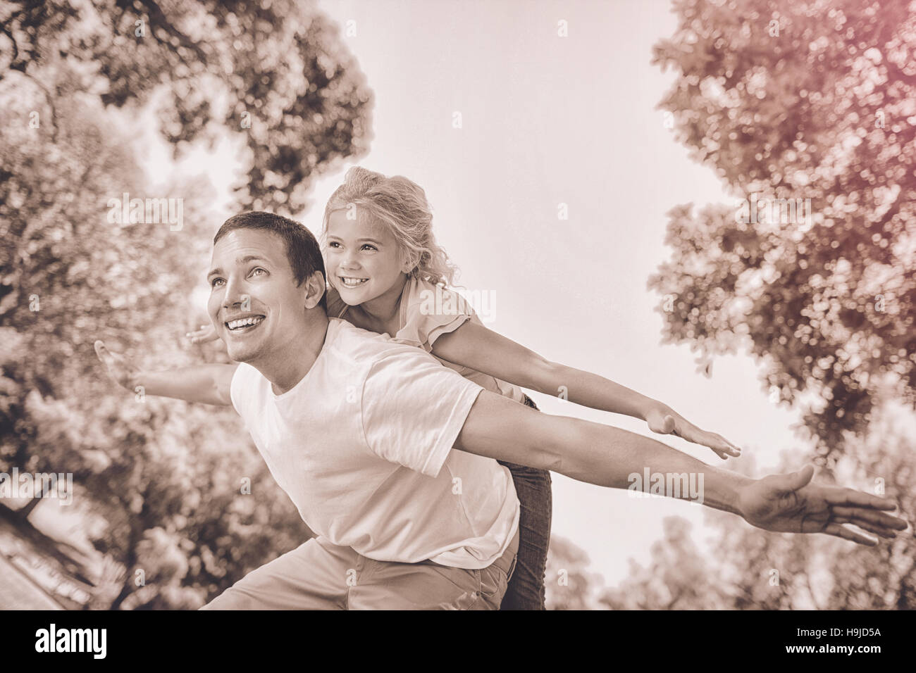 Father giving daughter un piggy back in park Photo Stock