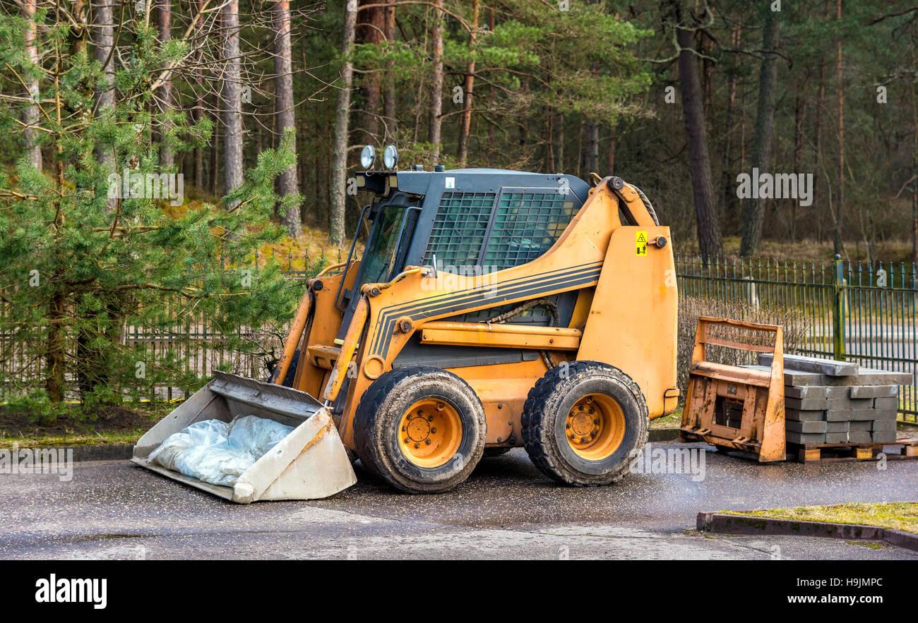 Bobcat ou chargeur skid garé en forêt Photo Stock