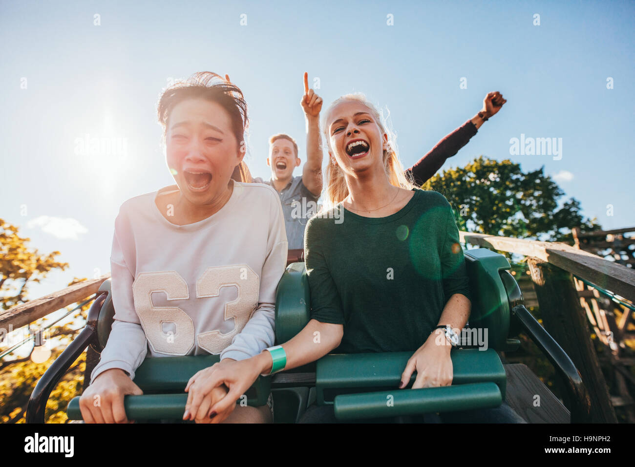 Jeunes amis enthousiaste équitation roller coaster ride at amusement park. Les jeunes s'amuser au parc Photo Stock