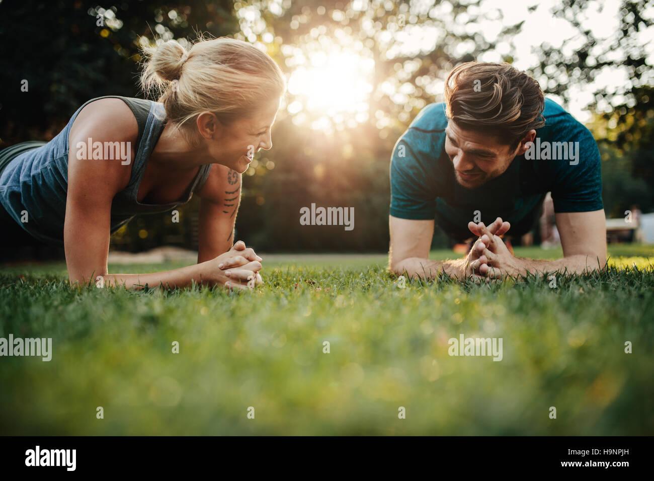 Fit young man and woman exercising in park. Smiling caucasian couple d'entraînement de base sur l'herbe. Banque D'Images