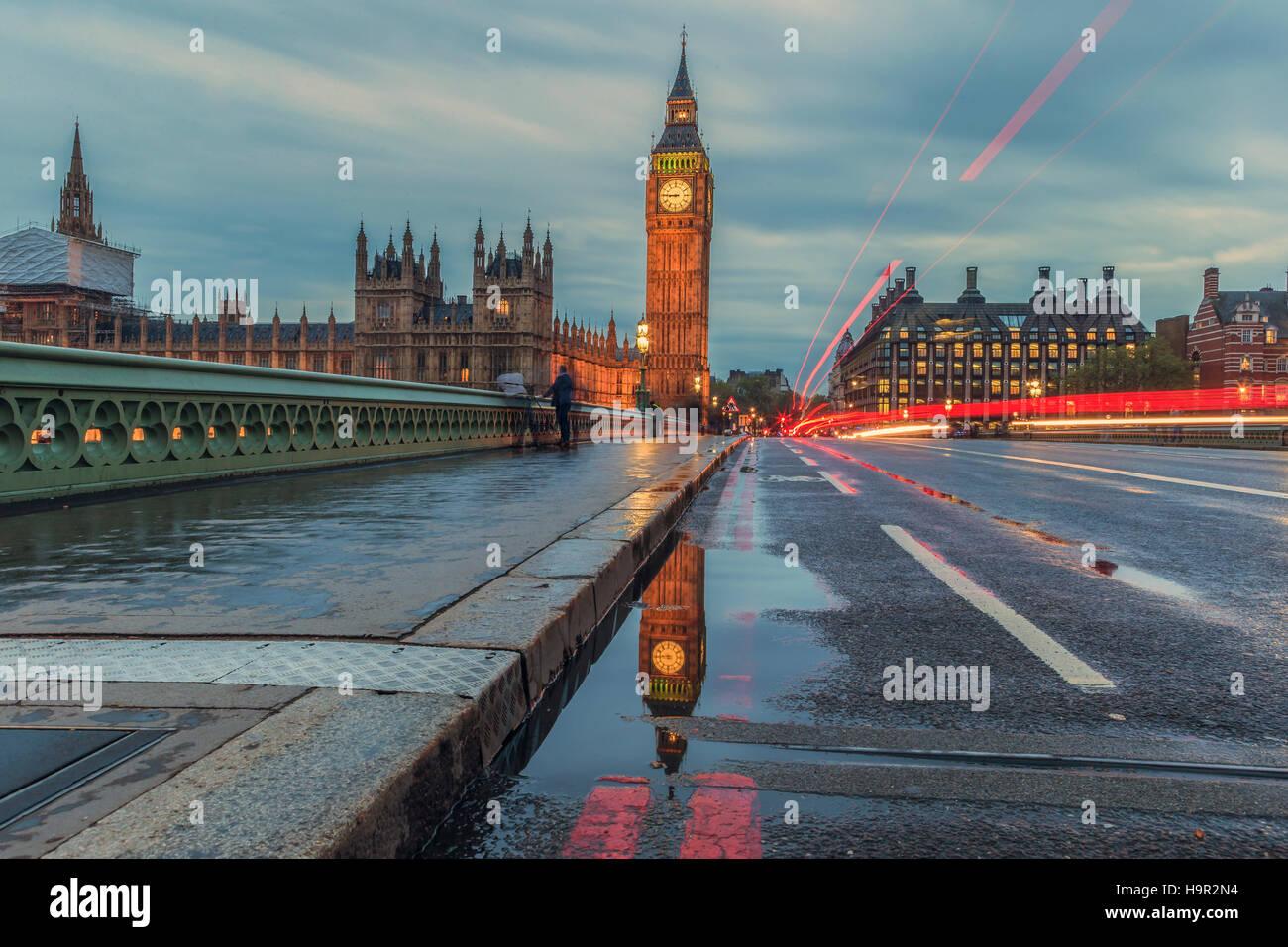 Une réflexion de Big Ben dans une flaque d'eau sur le pont de Westminster au crépuscule. Photo Stock