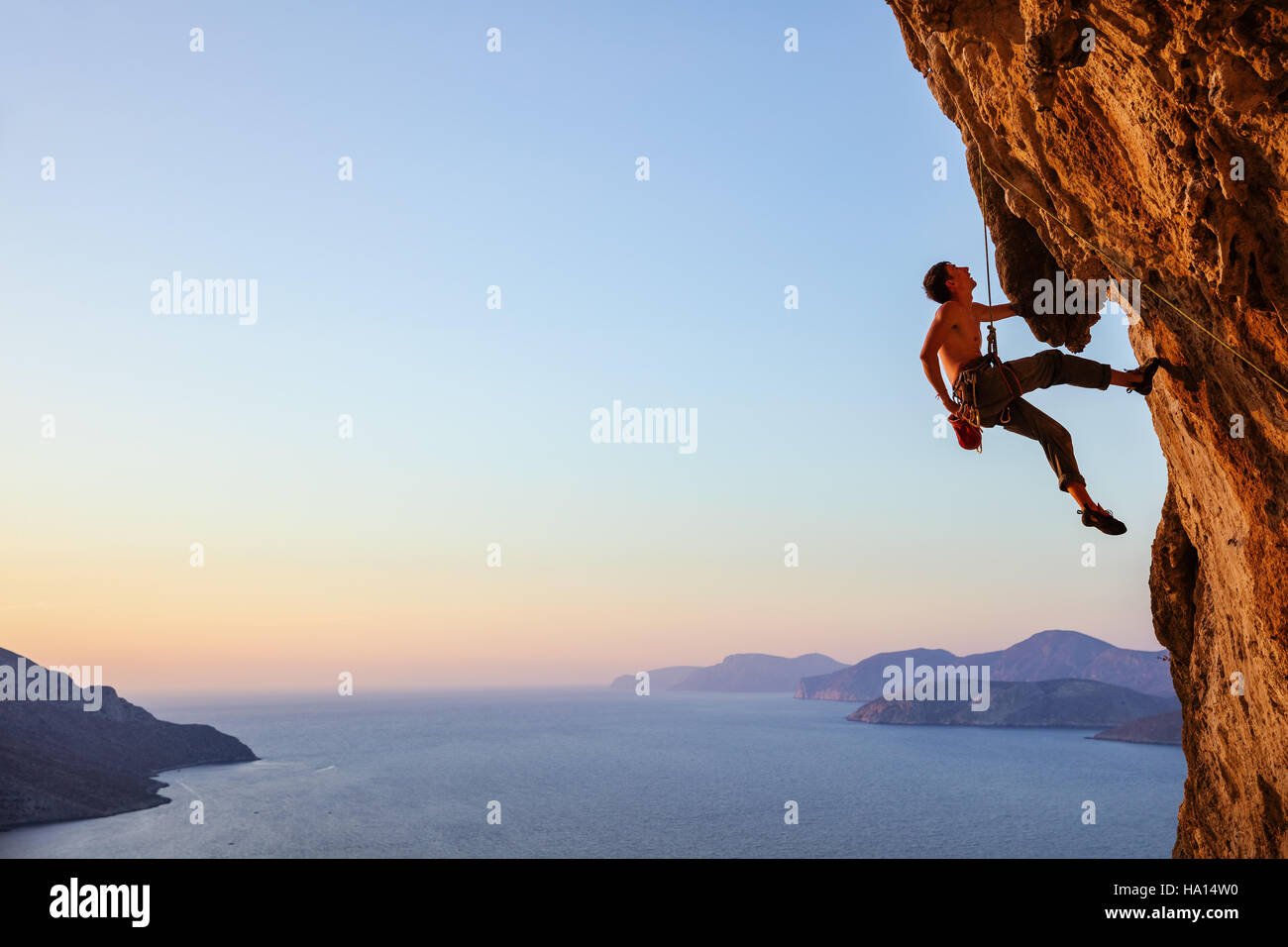 Rock climber resting alors que l'escalade falaise en surplomb Photo Stock