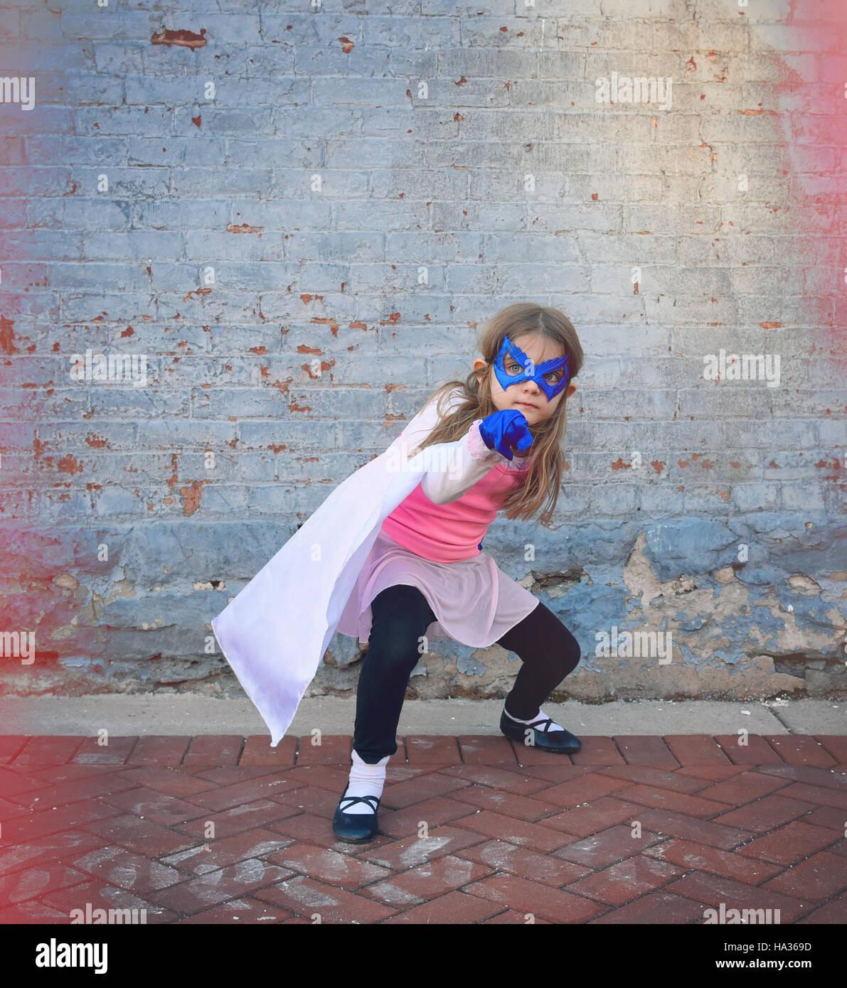 Un peu de super héros enfant est debout à l'extérieur contre un vieux millésime mur de brique Photo Stock