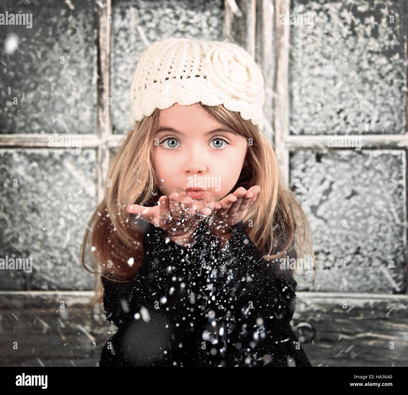 Un jeune enfant est blanc dans un souffle les flocons de l'hiver pour une scène d'arrière-plan ou de la saison de Noël de concept. Banque D'Images