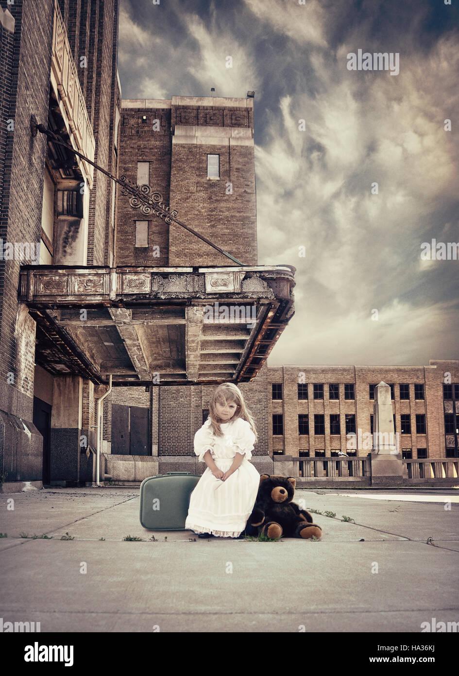Un petit enfant est assis sur une valise de voyage par un vieux bâtiment avec des ours en peluche à côté d'elle pour une force de protection ou de métaphore. Banque D'Images