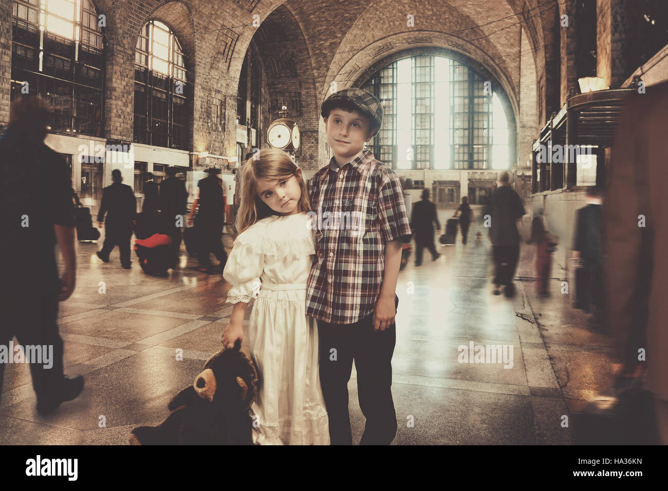 Deux jeunes enfants voyageur vintage sont debout dans une ancienne gare en attente de transport pour un voyage imaginaire ou le concept. Banque D'Images