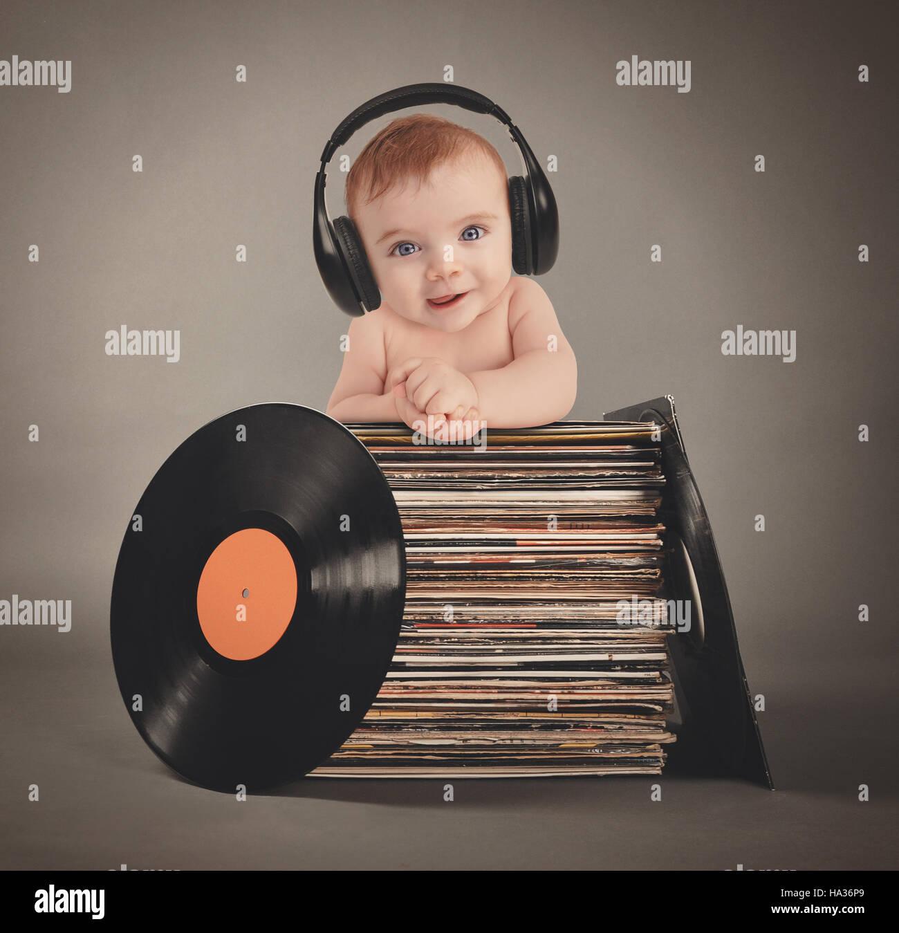 Un petit bébé porte des écouteurs de musique rétro avec les disques vinyles sur un fond gris pour un parti ou divertissement concept. Banque D'Images