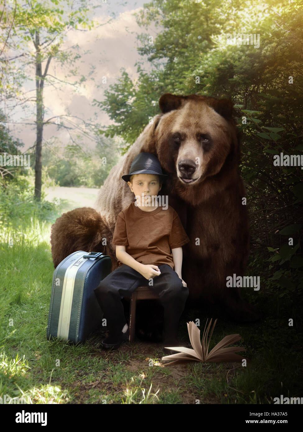 Un jeune garçon est assis sur un sentier dans les bois avec une valise et livre avec un ours animal derrière Photo Stock