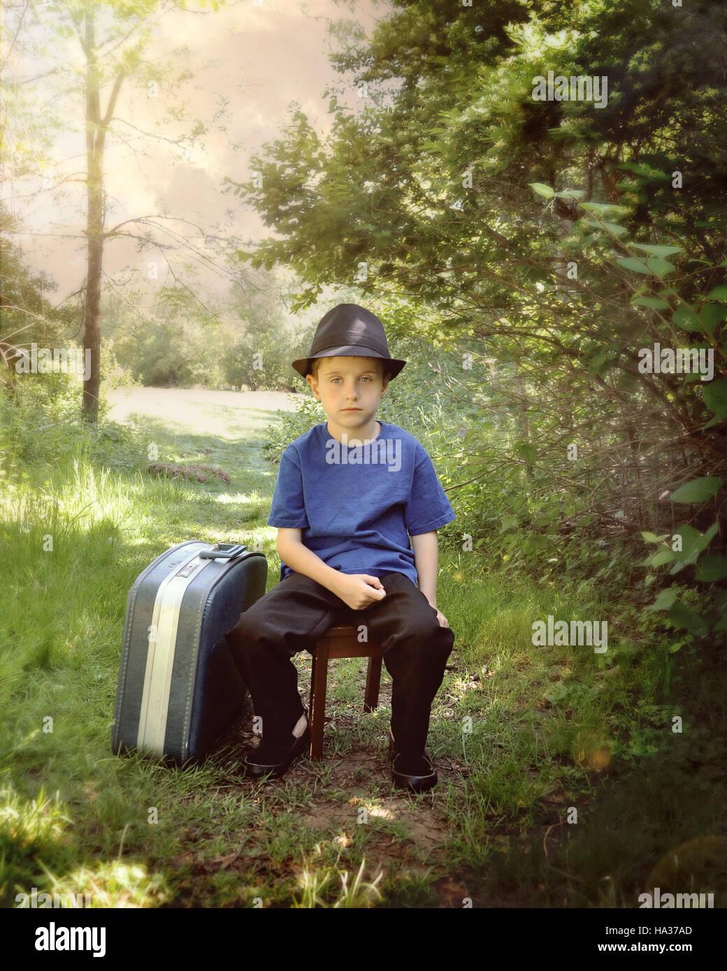 Un jeune garçon est assis sur un sentier dans les bois avec une valise et un chapeau. L'enfant l'air triste pour un voyage ou vacances. Banque D'Images