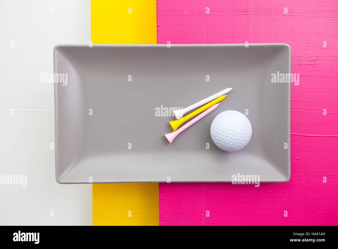Plat de céramique gris avec des équipements de golf sur plus de blanc, jaune et rose, table en bois plat Photo Stock