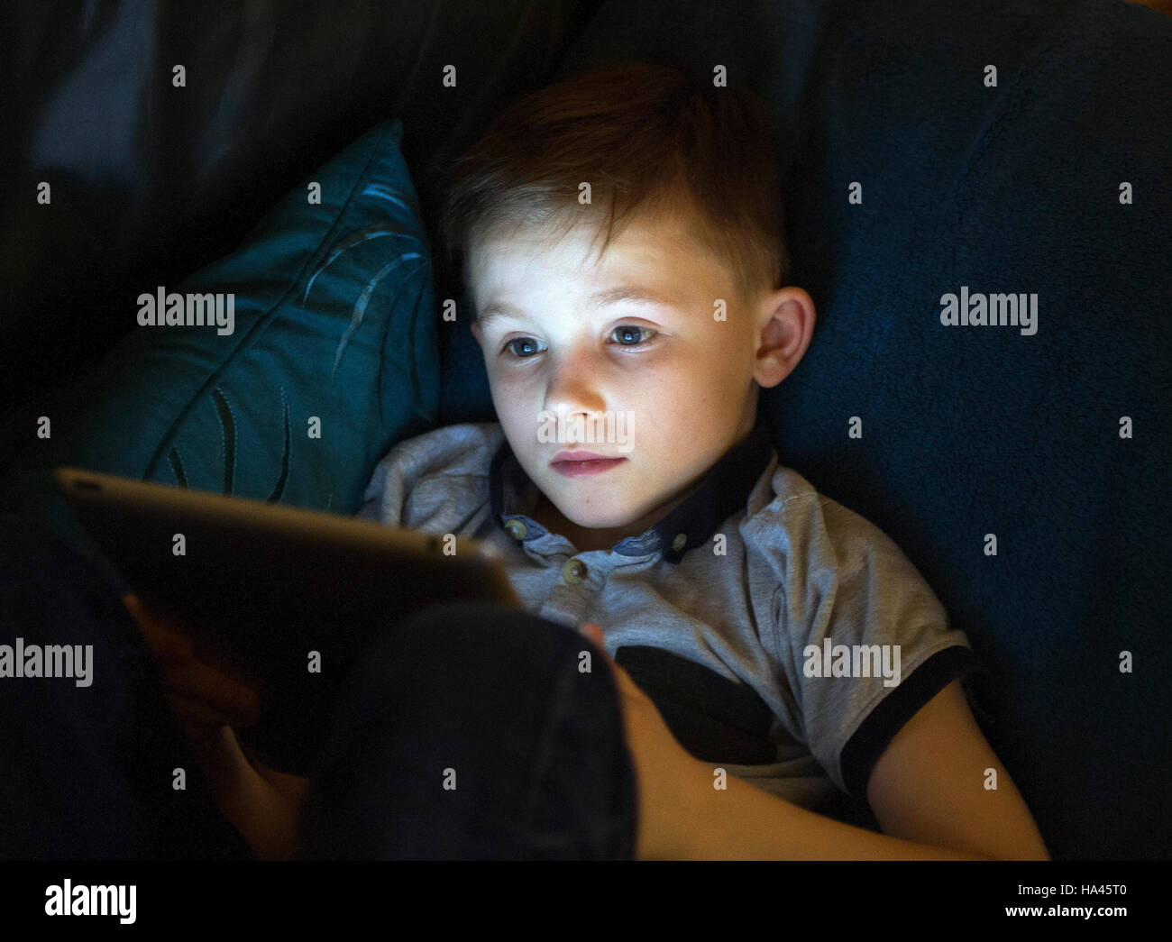 Jeune garçon assis à l'aide d'Apple l'ipad pour accéder à l'internet en utilisant Photo Stock