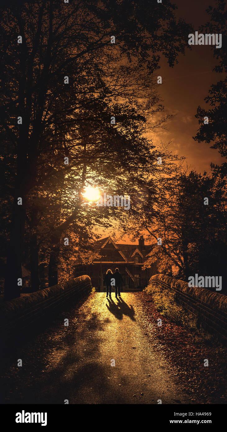 L'âge moyen en train de marcher sur le pont en parc avec la lumière au coucher du soleil Banque D'Images
