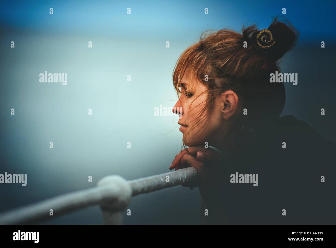 Jeune femme posant sa tête sur un poteau, face à la mer Photo Stock