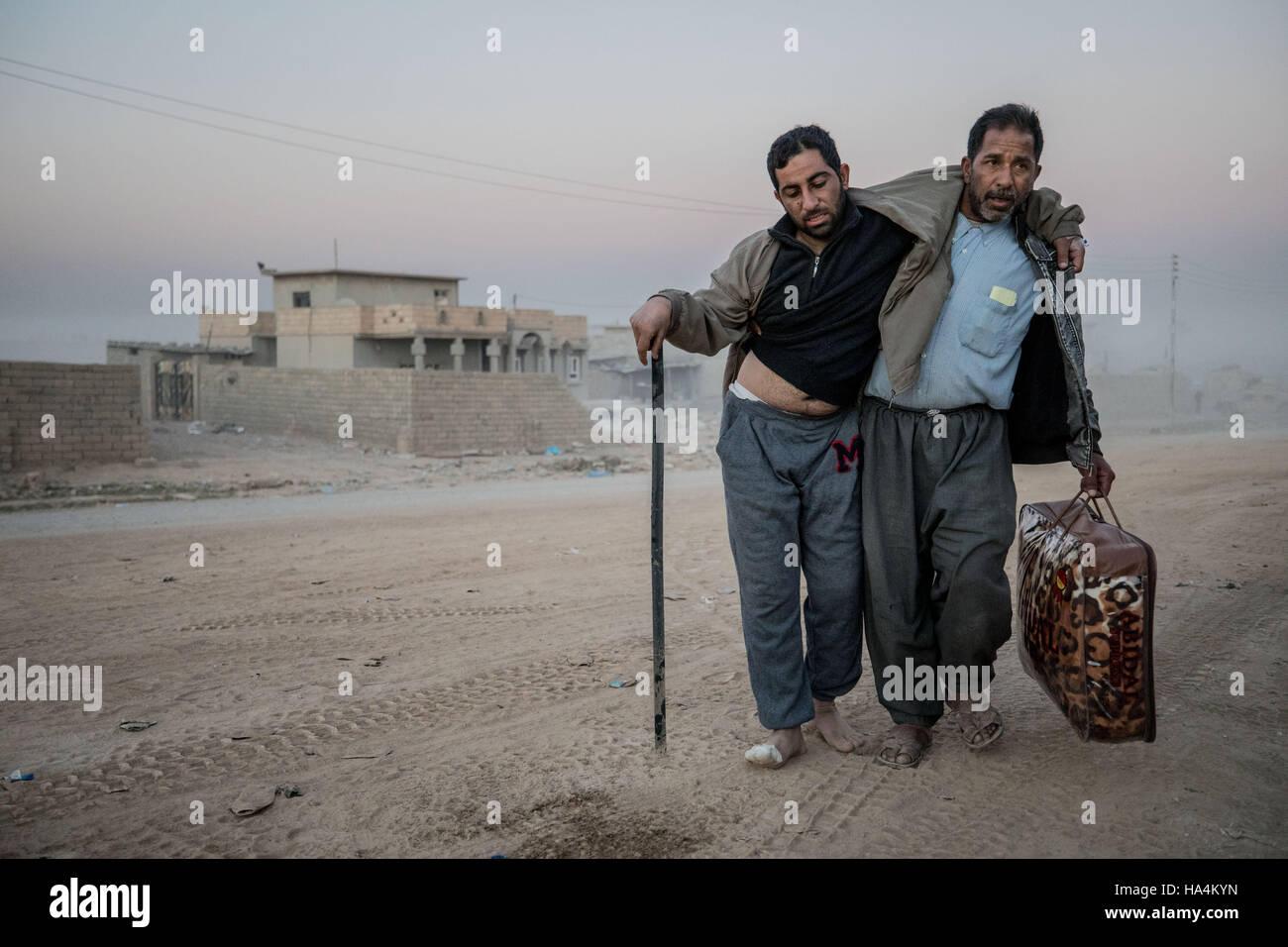 Mossoul, Ninive, Province de l'Irak. 26 Nov, 2016. Un homme aide son ami blessé le rendre à l'hôpital Photo Stock