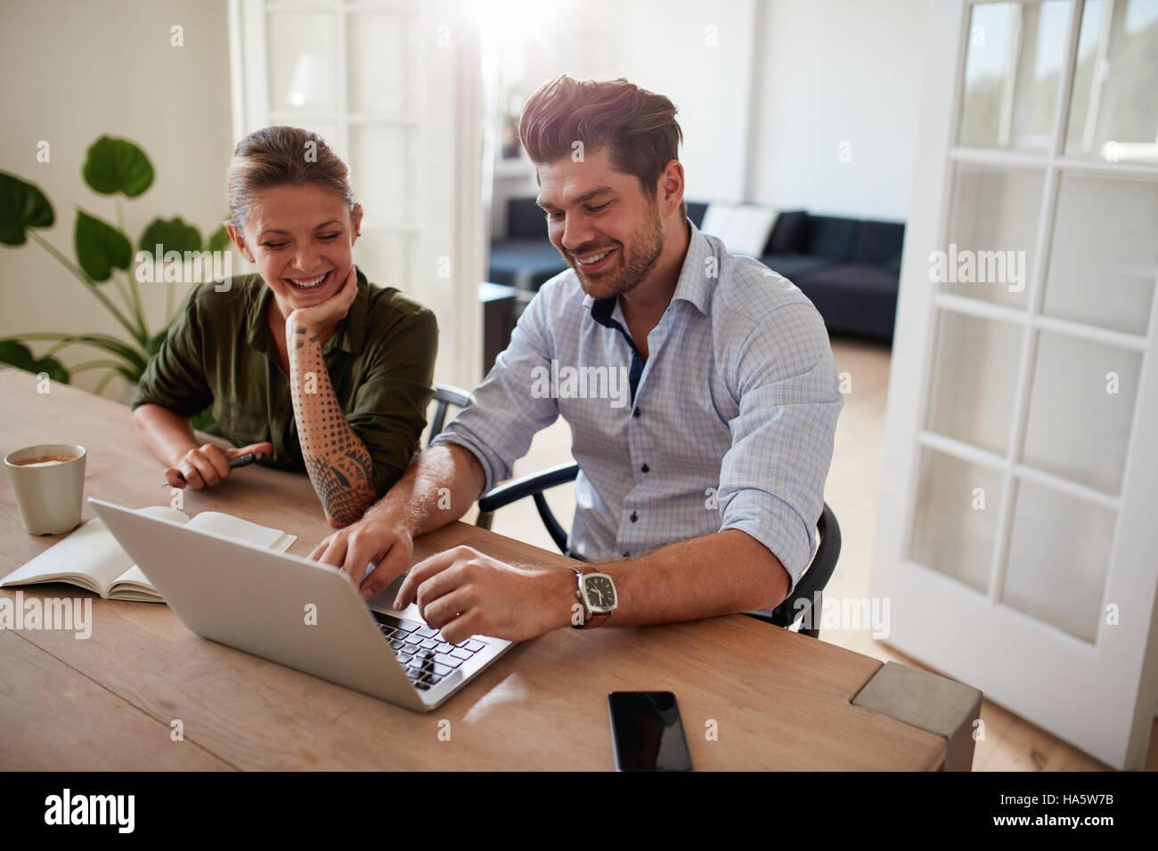 Coup de jeune couple assis ensemble et travailler sur ordinateur portable. Heureux jeune homme et femme à la maison Banque D'Images