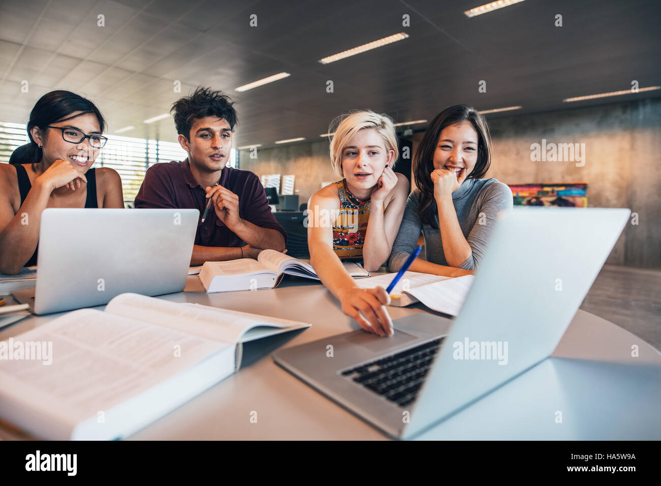 College students using laptop while sitting at table. L'étude en groupe de travail scolaire. Photo Stock