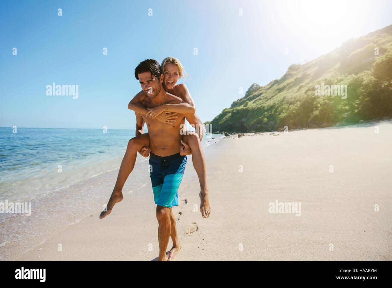 Portrait de l'homme exerçant son amie sur son dos le long du bord de mer. Man giving piggyback ride pour Photo Stock