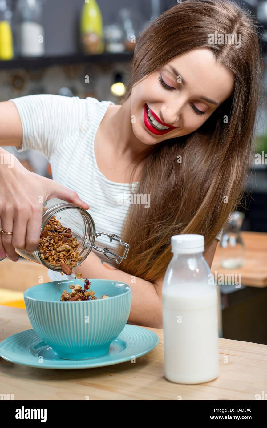 Femme avec des céréales petit-déjeuner dans la cuisine Photo Stock