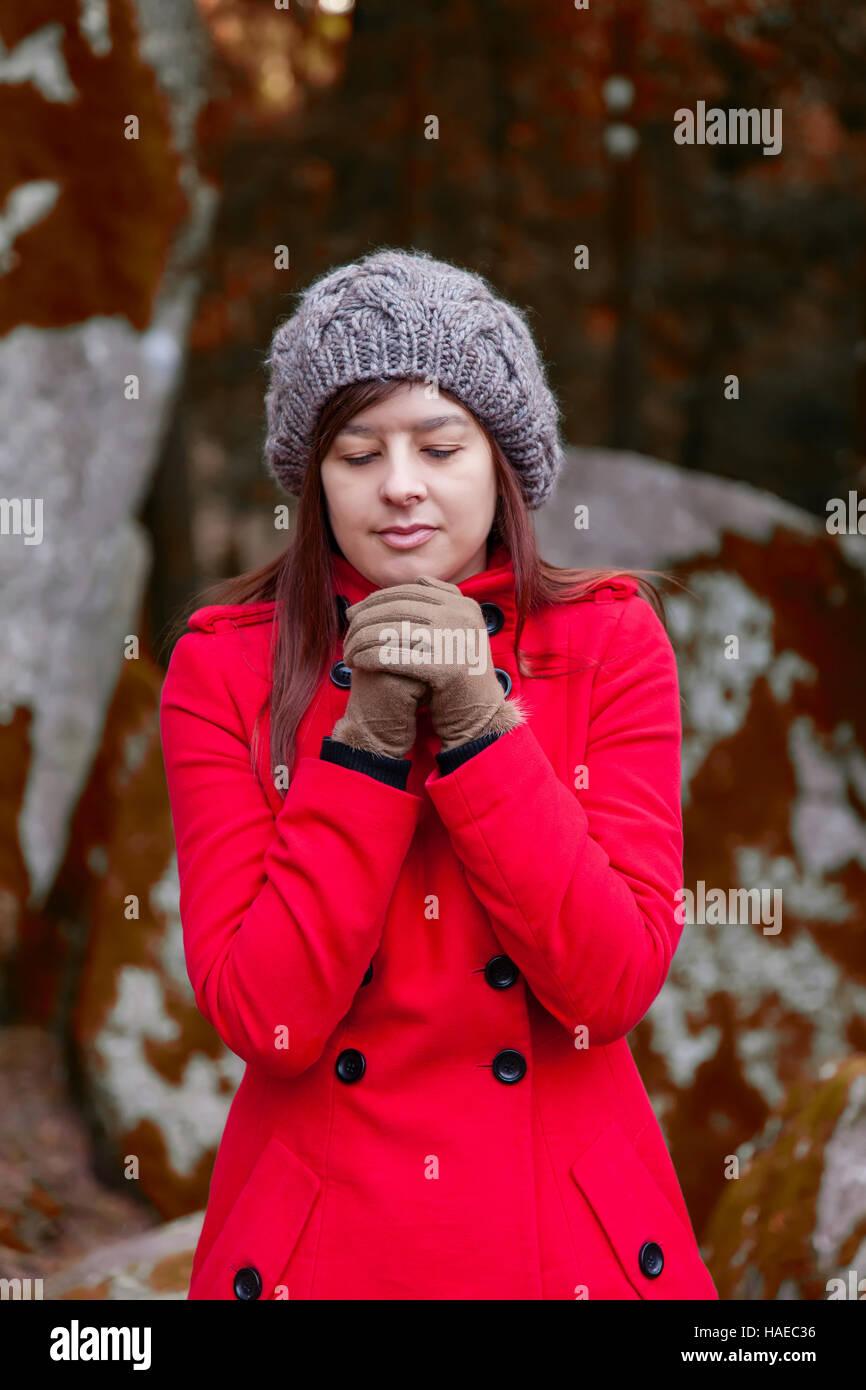 Jeune femme tremblant de froid sur une forêt portant un manteau, un bonnet  et des 6a0cd70f4e6