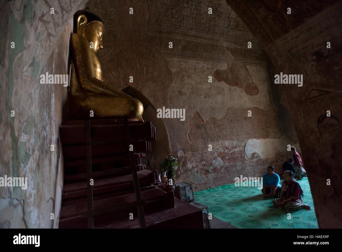 Les gens priant devant une statue de Bouddha en or à la temple Sulamani à Bagan, Myanmar. Photo Stock