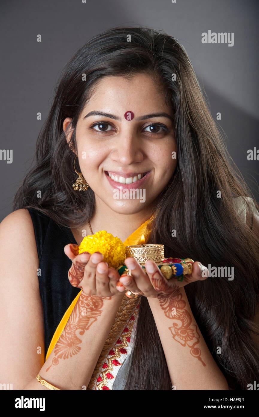 Une fille souriante et tenant une lampe à huile traditionnelle Diwali diya avec fleur offrande religieuse et souriant Mumbai Inde Banque D'Images