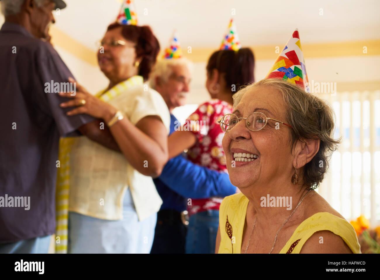 Groupe de vieux amis et famille célébrant les hauts d'anniversaire en maison de retraite. Woman smiling Photo Stock