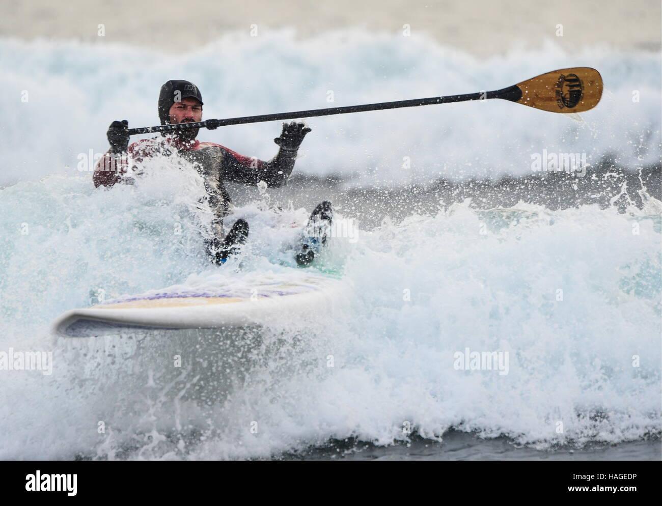 Vladivostok, Russie. 1er décembre 2016. Un homme monté sur une vague sur stand up paddle board dans l'Oussouri Photo Stock