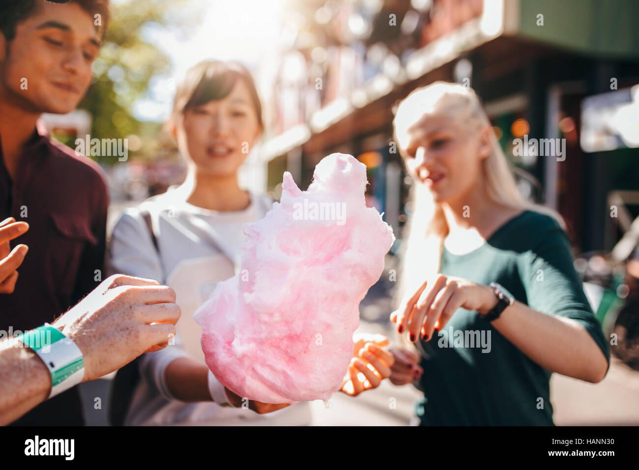 Trois jeunes personnes candyfloss coton au parc d'amusement. Groupe d'amis de manger de la barbe à l'extérieur ensemble. Banque D'Images