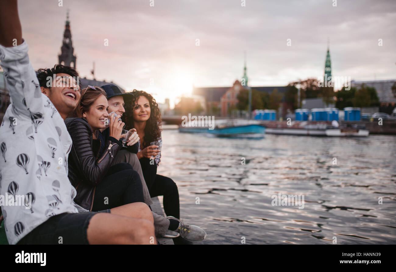 Photo de groupe des gens assis en plein air sur la jetée ou d'avoir du plaisir. Amis de la jetée sur le lac de la Banque D'Images