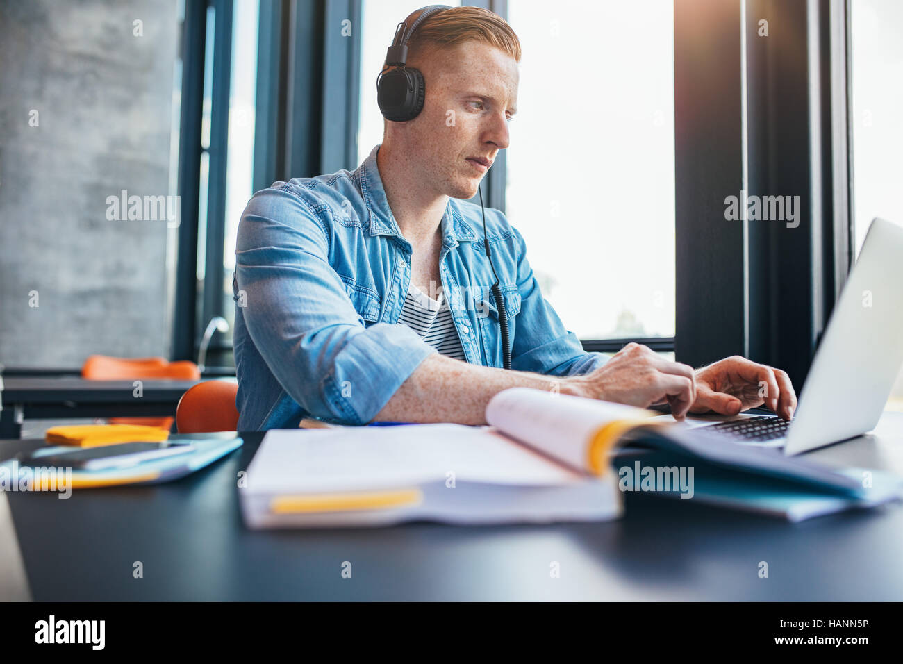 Shot of young caucasian man with headphones studying in library à l'aide d'ordinateur portable. Étudiant de l'université Banque D'Images